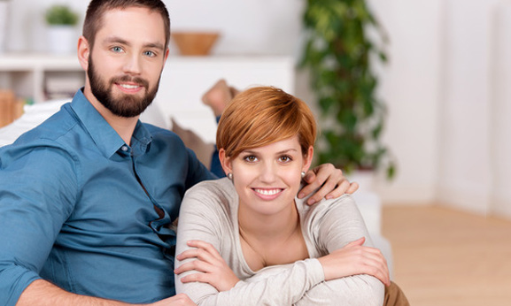 Airconditioning at home Portrait of young couple relaxing on sofa at home